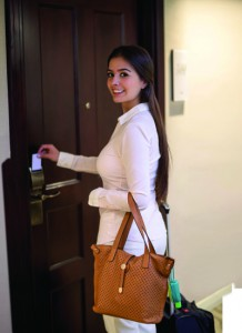 Woman at a hotel opening the door with a cardkey and looking at the camera smiling